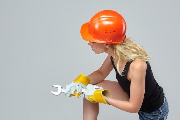 Blonde frau. in einem schutzhelm und handschuhen mit einem großen schraubenschlüssel.