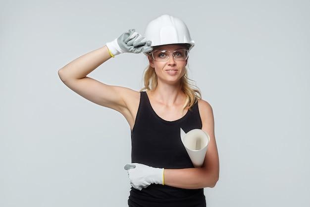 Blonde frau. in einem weißen schutzhelm hält ein projekt in seinen händen. baukonzept