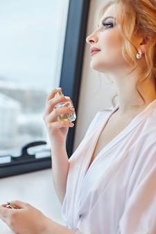 Blonde frau in einer weißen seidenrobe spritzt parfüm