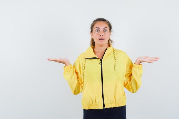 Blonde frau in gelber bomberjacke und schwarzer hose streckt fragend die hände und sieht verblüfft aus Kostenlose Fotos