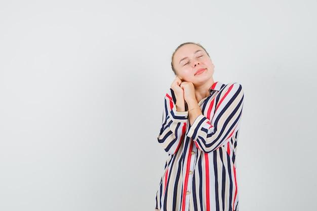 Blonde frau in gestreifter bluse lehnte ihre wange auf handfläche und sah entspannt aus