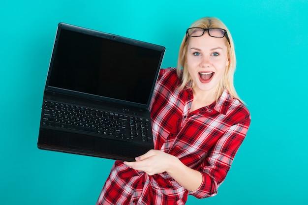 Blonde frau in gläsern halten laptop