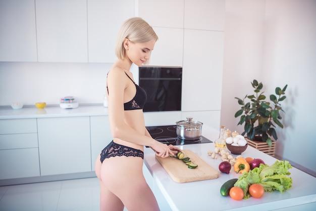 Blonde frau in ihren dessous posiert in der küche