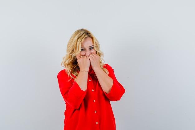 Blonde frau in roter bluse beißt fäuste und schaut ängstlich, vorderansicht.