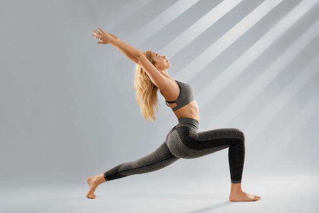 Blonde frau in trendiger sportkleidung macht yogaübungen