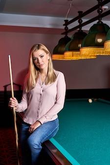 Blonde frau kam, um angenehme zeit mit snooker zu verbringen, sie posiert vor der kamera, sitzt am pool, billardtisch