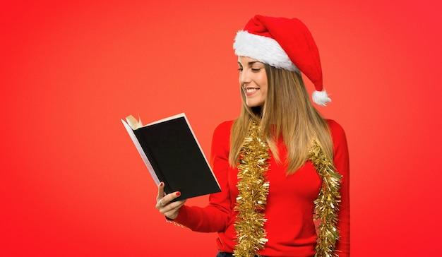 Blonde frau kleidete oben für die weihnachtsfeiertage an, die ein buch halten und das ablesen auf rotem hintergrund genießen