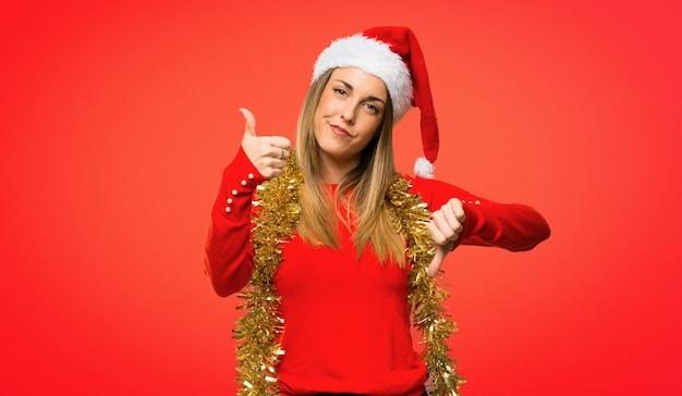 Blonde frau kleidete oben für die weihnachtsfeiertage an, die gut-schlechtes zeichen machen