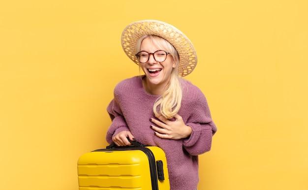 Blonde frau lacht laut über einen lustigen witz, fühlt sich glücklich und fröhlich und hat spaß