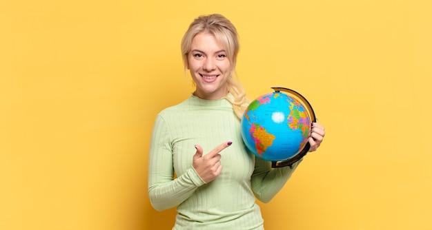 Blonde frau lächelt fröhlich, fühlt sich glücklich und zeigt zur seite und nach oben, zeigt objekt im kopierraum