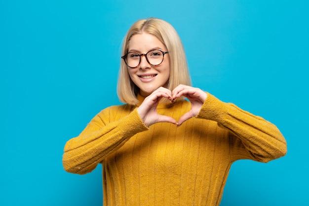 Blonde frau lächelt und fühlt sich glücklich, süß, romantisch und verliebt, macht herzform mit beiden händen