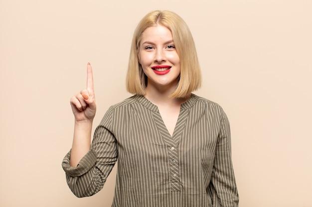 Blonde frau lächelt und sieht freundlich aus, zeigt nummer eins oder zuerst mit der hand nach vorne, countdown