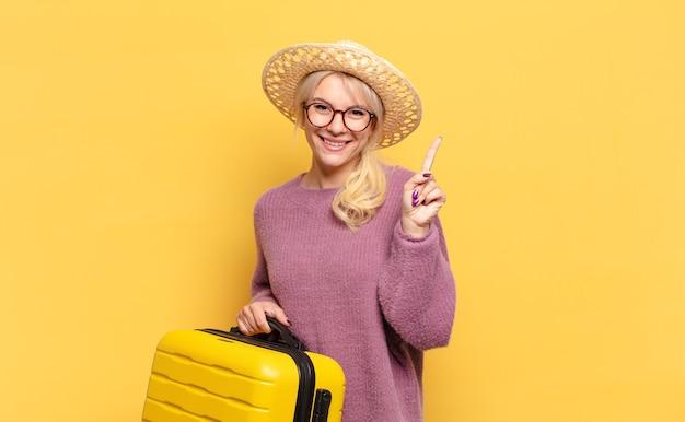 Blonde frau lächelt und sieht freundlich aus, zeigt nummer eins oder zuerst mit der hand nach vorne, zählt herunter
