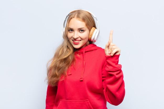 Blonde frau lächelt und sieht freundlich aus, zeigt nummer eins oder zuerst mit der hand showing