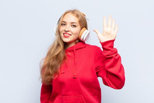 Blonde frau lächelt und sieht freundlich aus, zeigt nummer fünf oder fünfte mit der hand nach vorne, countdown