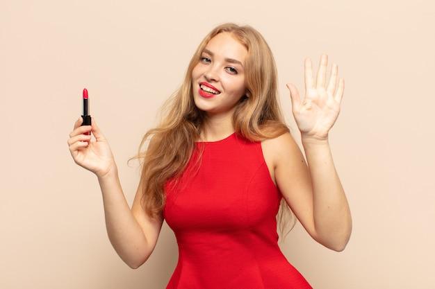 Blonde frau lächelt und sieht freundlich aus, zeigt nummer fünf oder fünfte mit der hand nach vorne und zählt herunter