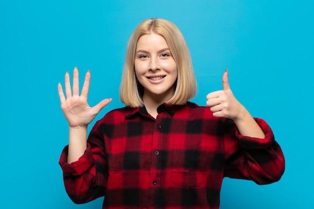 Blonde frau lächelt und sieht freundlich aus, zeigt nummer sechs oder sechste mit der hand nach vorne, countdown