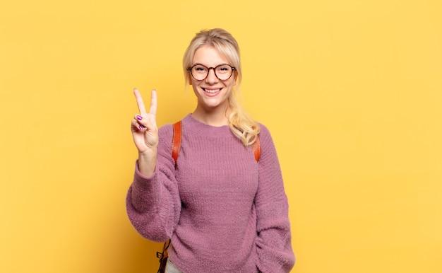 Blonde frau lächelt und sieht freundlich aus, zeigt nummer zwei oder sekunde mit der hand nach vorne, countdown
