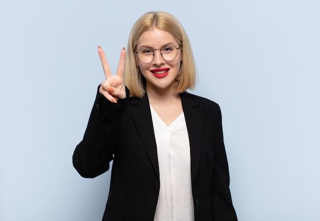 Blonde frau lächelt und sieht glücklich, sorglos und positiv aus, gestikuliert sieg oder frieden mit einer hand