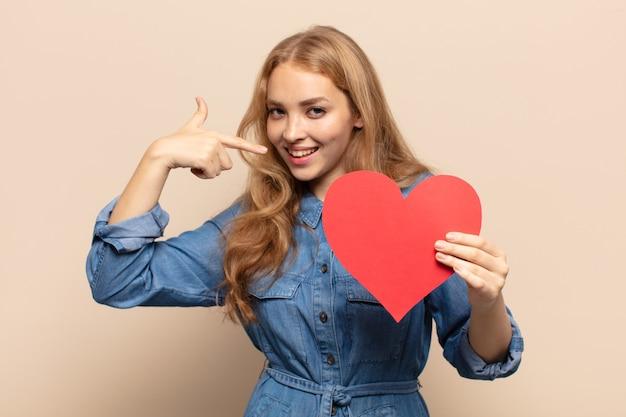 Blonde frau lächelt zuversichtlich und zeigt auf ein eigenes breites lächeln, positive, entspannte, zufriedene haltung