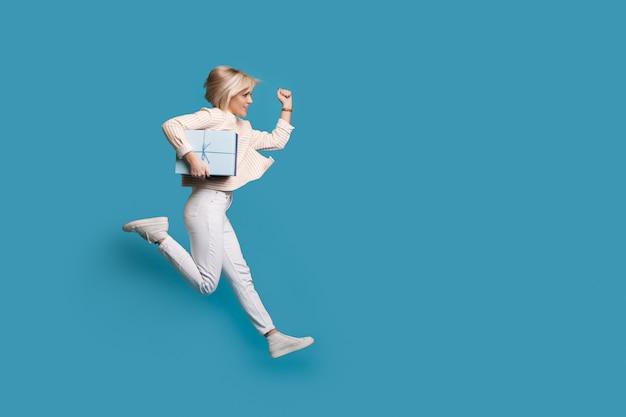Blonde frau läuft auf einer wand mit blauem freiem raum, der eine geschenkbox in händen hält