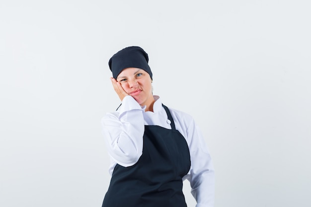 Blonde frau lehnt wange auf handfläche, verzieht das gesicht in schwarzer kochuniform und sieht unzufrieden aus, vorderansicht.
