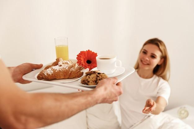 Blonde frau liegt im bett und betrachtet tablett mit frühstück und nimmt es