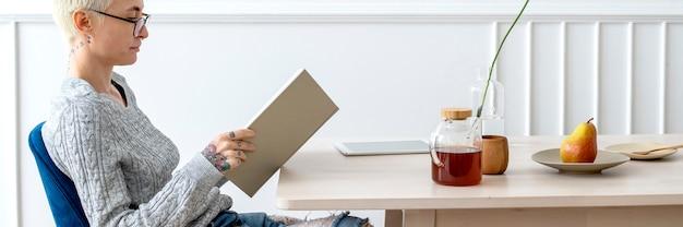 Blonde frau liest ein buch in einem wohnzimmer