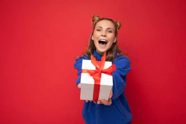 Blonde frau lokalisiert über rote hintergrundwand, die blauen trendigen hoodie hält, der geschenkbox hält und kamera und schreien betrachtet.