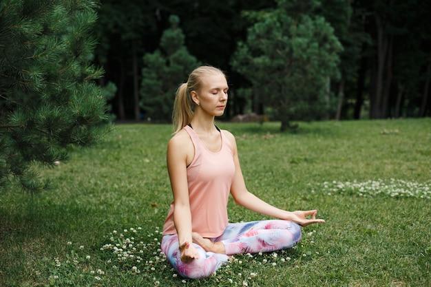Blonde frau meditiert über grünes gras