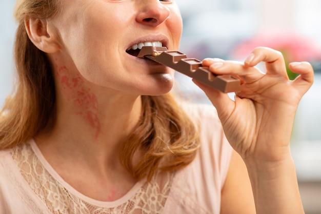 Blonde frau mit ausschlag am hals und starker allergie beim essen von schokolade