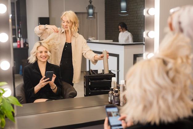 Blonde frau mit dem handy, der ihr haar erledigt erhält