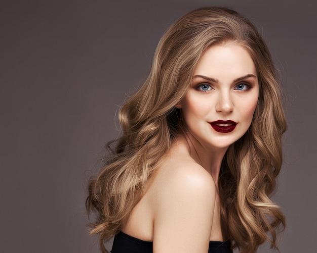 Blonde frau mit dem lockigen schönen haar lächelnd auf grauem hintergrund.