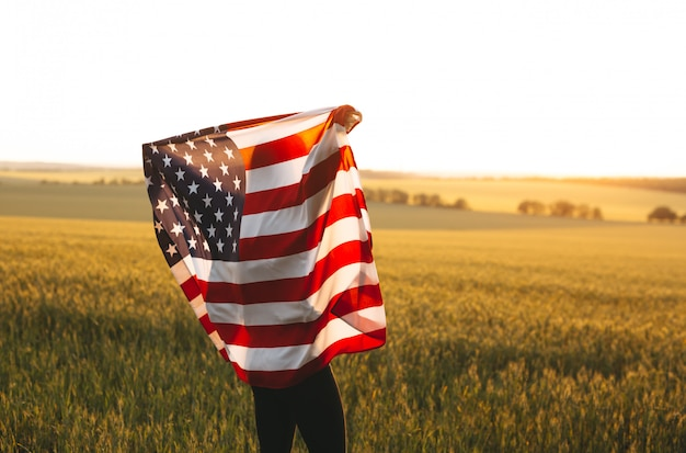 Blonde frau mit der amerikanischen flagge, die in einem weizenfeld bei sonnenuntergang läuft. unabhängigkeitstag, patriotischer feiertag. 4. juli.