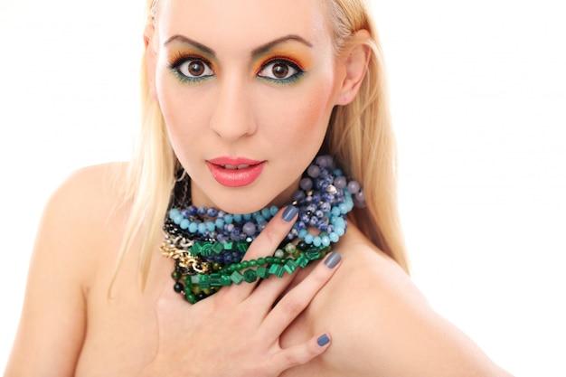 Blonde frau mit der halskette, die ihren netten farbigen blick zeigt
