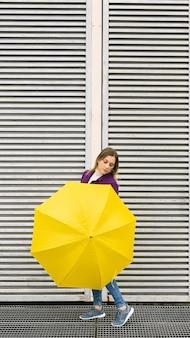 Blonde frau mit einem gelben regenschirm, der vor einer weißen wand mit einer geometrischen struktur aufwirft.