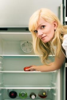 Blonde frau mit einem leeren kühlschrank
