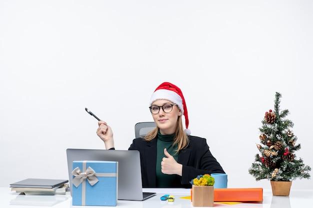 Blonde frau mit einem weihnachtsmannhut, der an einem tisch mit einem weihnachtsbaum und einem geschenk sitzt
