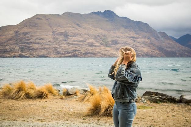 Blonde frau mit einer jeansjacke, die nahe dem welligen meer steht, umgeben von hohen felsigen bergen