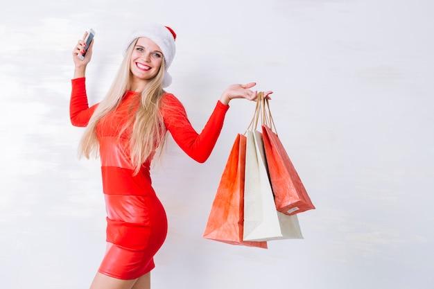 Blonde frau mit einkaufstaschen und telefon