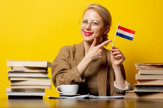 Blonde frau mit flagge der niederlande und bücher auf gelb