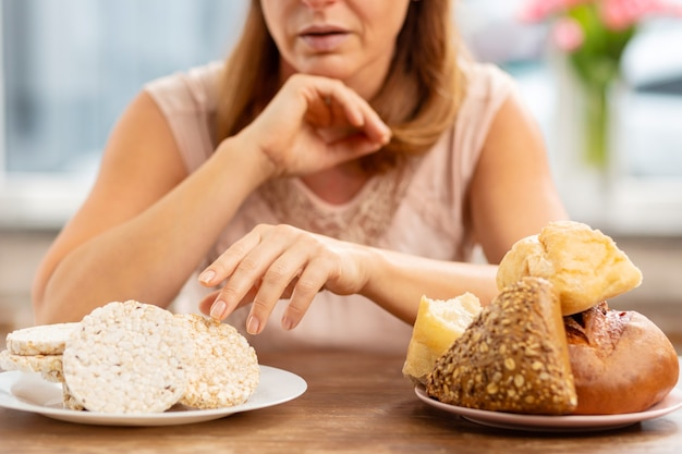 Blonde frau mit glutenallergie, die wenig knuspriges brot oder brötchen nimmt