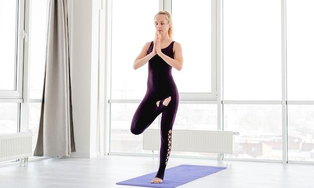 Blonde frau mit guter körperform, die während des yoga-trainings in der baumhaltung bleibt