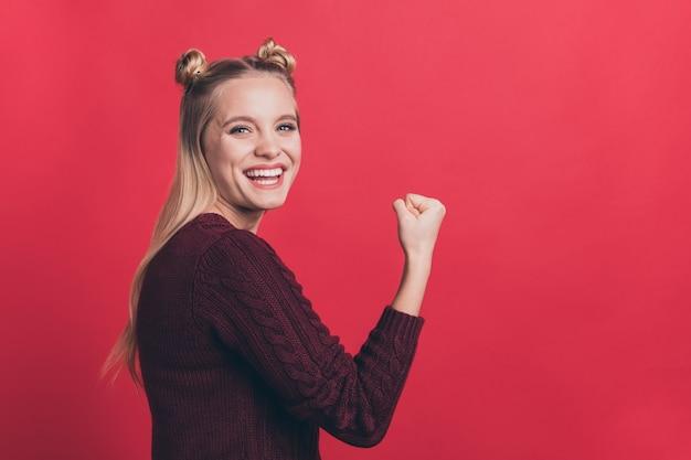 Blonde frau mit haarknoten posiert gegen die rote wand