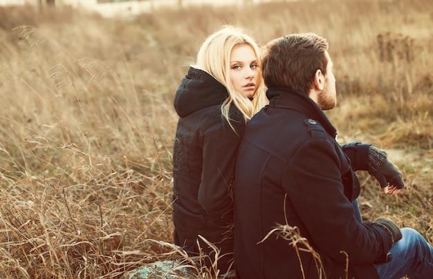 Blonde frau mit ihrem partner auf der wiese sitzt