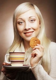 Blonde frau mit kaffee und keksen