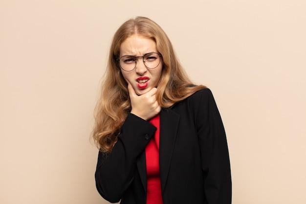 Blonde frau mit offenem mund und weit geöffneten augen und hand am kinn, die sich unangenehm geschockt fühlt und sagt, was oder wow