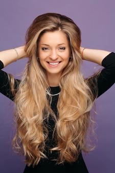 Blonde frau mit perfektem make-up und voluminösem haar nach schönheitssalon