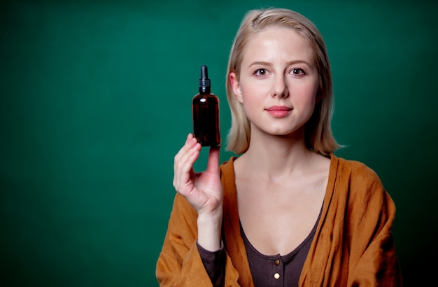 Blonde frau mit schwarzer flasche auf grüner szene