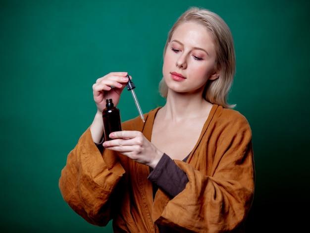 Blonde frau mit schwarzer flasche und pipette auf grüner szene